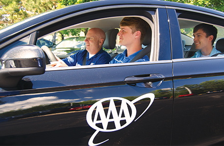 Two teenagers in a car with an AAA Driver Training instructor