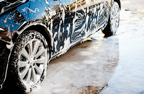 Picture of the bottom portion of a car covered in soap and suds