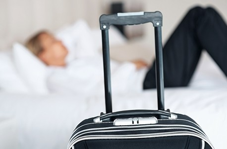 man with luggage in hotel room
