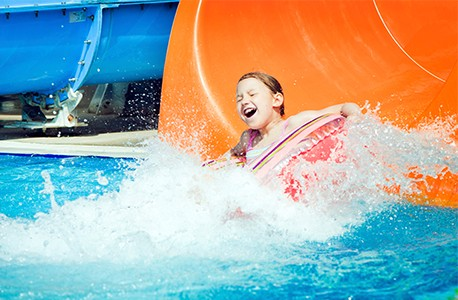 Child riding tube down water slide
