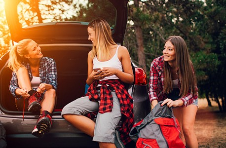 3 women behind car in outdoors