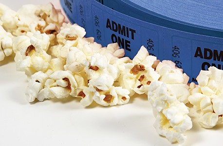 A roll of tickets surrounded by popcorn