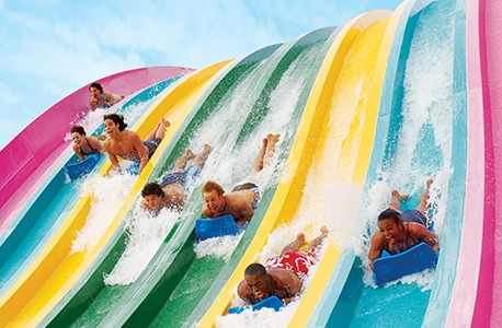 Young adults sliding down a set of rainbow colored waterslides