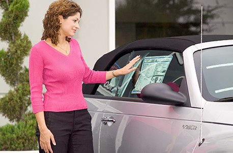Woman looking at pricing information posted in vehicle window
