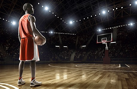 Basketball player on a court with the lights dimmed and spectators watching