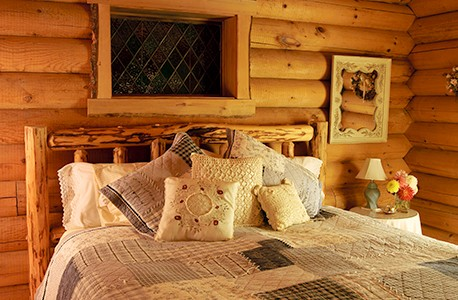 A bed in a hotel room with a log-cabin feel