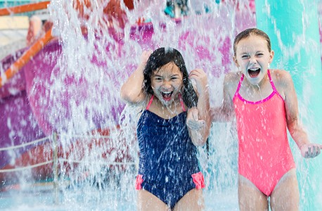 Two young girls playing in a waterpark, standing under falling water