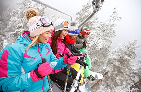 Four AAA Members riding a ski lift with snowy trees in the background.