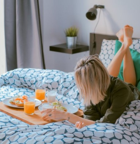 woman in hotel room eating breakfast in bed