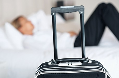A close-up of a suitcase with a person laying on a hotel bed in the background