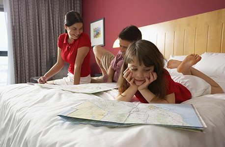 A child and two adults laying on a hotel bed looking at maps.