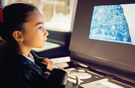 Young girl looking at an interactive museum exhibit