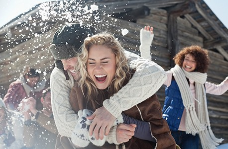 Adults dressed in winter clothing having fun in the snow